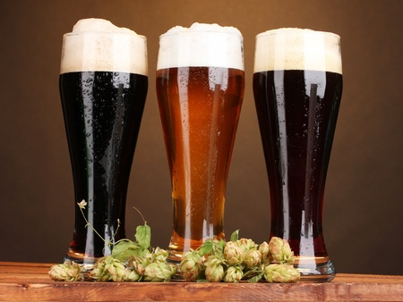 three glasses with different beers and hop on wooden table on brown background Stock Photo - 11832152