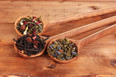 Different kinds of green and black dry tea in spoons on wooden table photo