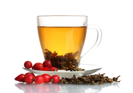 Green tea  with red viburnum and  hips in glass cup isolated on white