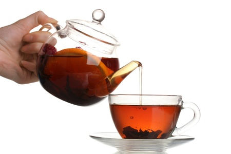 Glass teapot pouring black tea into cup isolated on white photo