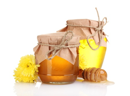 two jars of honey and wooden drizzler isolated on white photo
