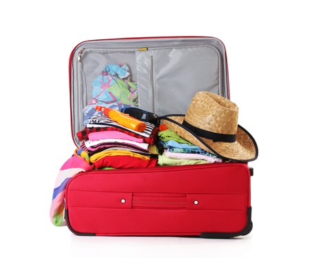 Open red suitcase with clothing isolated on a white photo