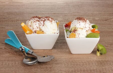 delicious vanilla ice cream with chocolate and fruits in bowls and spoons on wooden background photo