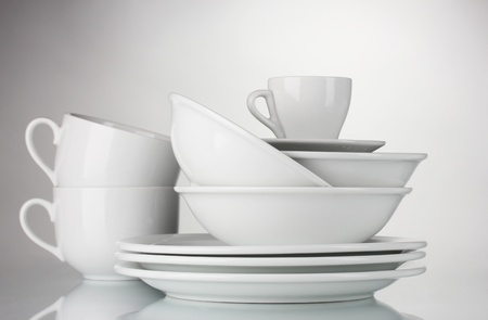 empty bowls, plates and cups on gray background