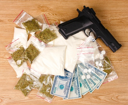 illicit: Cocaine and marihuana in packages, dollars and handgun on wooden background Stock Photo