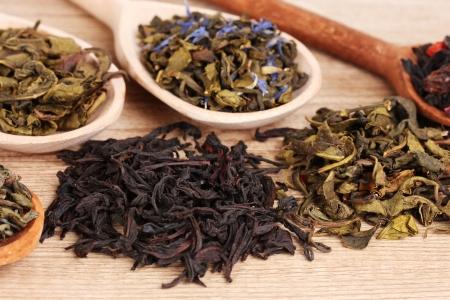 teepflanze: Verschiedene Arten von trockenen gr�nem und schwarzem Tee im L�ffel auf Holzuntergrund