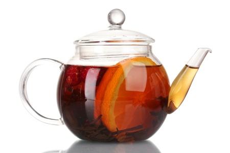 Glass teapot with black tea and orange isolated on white photo