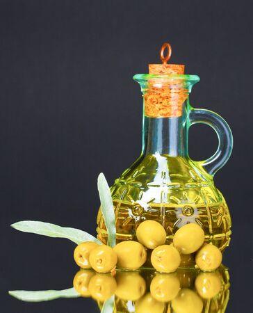 olive oil in jar and olives on black background photo