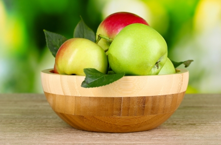 apple basket: Fresh organic apples in plate on wooden table outside Stock Photo