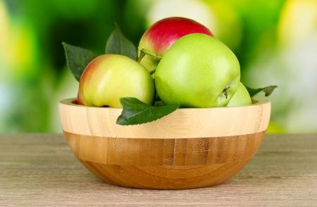 pomme jaune: Pommes organiques fra�ches dans la plaque sur la table en bois � l'ext�rieur