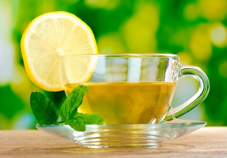 green water: tea with lemon on green leaves background