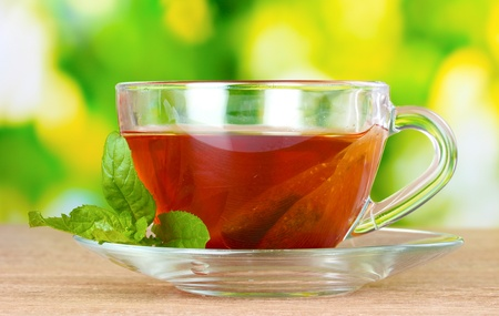 nice cup of tea and mint on green background photo