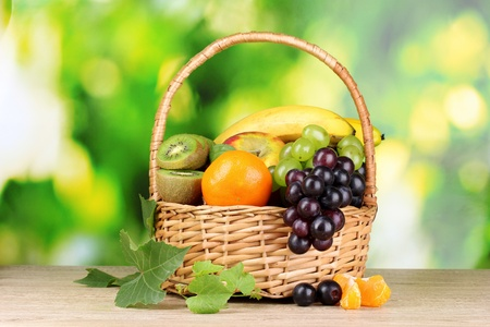 Ripe juicy fruits in basket on wooden table on green background photo