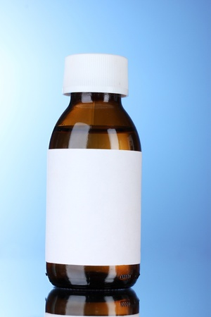 Liquid medicine in glass bottle and pills on blue background photo