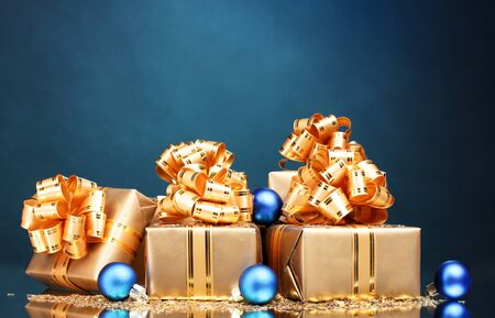 Beautiful gifts in gold packaging and Christmas balls on blue background photo