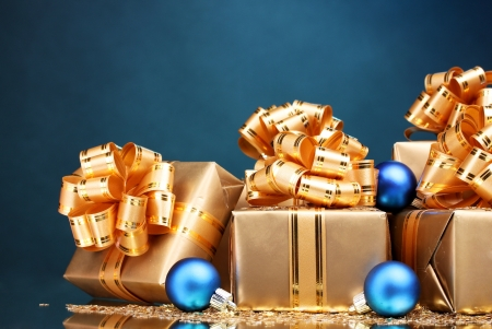 Beautiful gifts in gold packaging and Christmas balls on blue background Stock Photo - 11912056