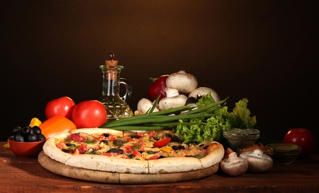 gourmet pizza: delicious pizza, vegetables and spices on wooden table on brown background