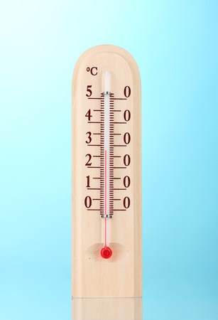 Wooden thermometer on blue photo