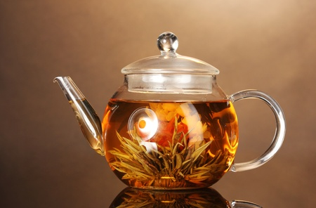 glass teapot with exotic green tea on wooden table on brown background Stock Photo