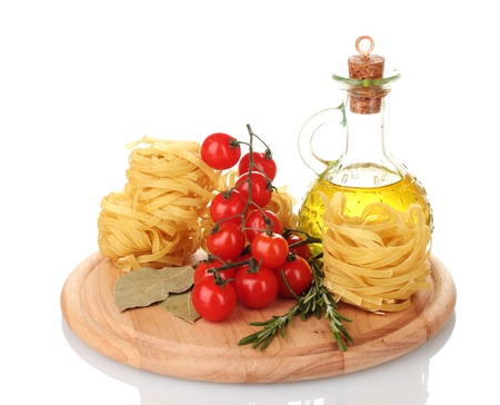 noodles, jar of oil, spices and vegetables on wooden board isolated on white photo