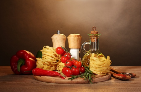 noodles in bowl, jar of oil, spices and vegetables on wooden table on brown background Stock Photo