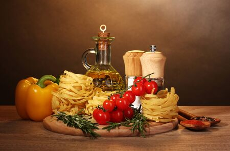 noodles in bowl, jar of oil, spices and vegetables on wooden table on brown background Stock Photo - 11912253
