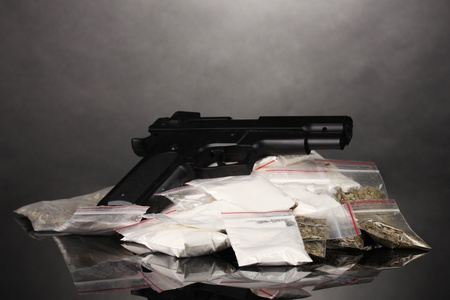 illicit: Cocaine and marihuana in packages and handgun on grey background Stock Photo