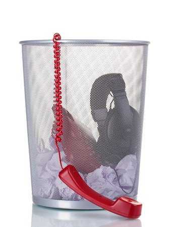 meaningless: red phone,headphones and paper in metal trash bin isolated on white