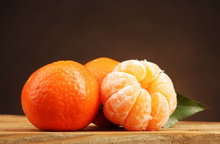 tangerines with leaf on wooden table on brown background photo