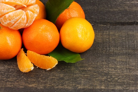 tangerines with leaves on wooden grey table photo