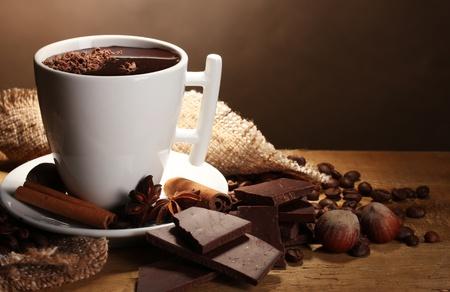 chocolate caliente: taza de chocolate caliente, los palitos de canela, nueces y chocolate en la mesa de madera sobre fondo marr�n Foto de archivo