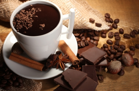 cocoa bean: cup of hot chocolate, cinnamon sticks, nuts and chocolate on wooden table Stock Photo