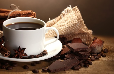 coffee cup and beans, cinnamon sticks, nuts and chocolate on wooden table on brown background photo
