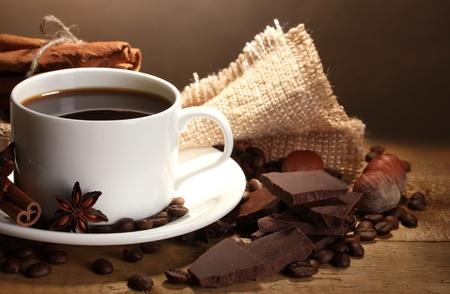 kopje koffie en bonen, kaneelstokjes, noten en chocolade op houten tafel op bruine achtergrond Stockfoto
