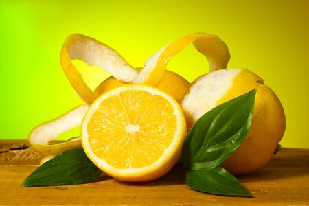 ascorbic: ripe lemons with leaves on wooden table on green background