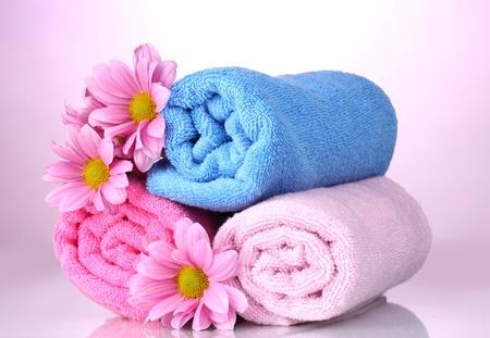 toallas: toallas y hermosas flores sobre fondo rosa Foto de archivo
