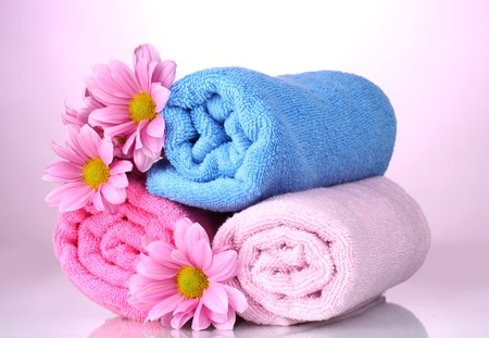 white towel: towels and beautiful flowers on pink background Stock Photo
