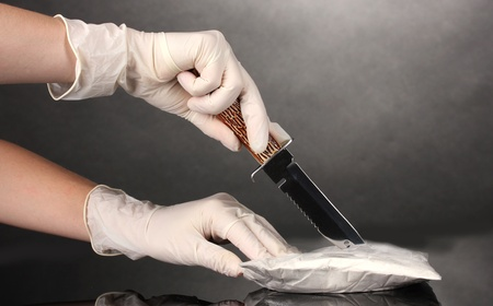 smuggling: packets of Cocaine opening with a knife on grey background