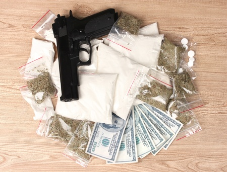 drug deals: Cocaine and marihuana in packages, dollars and handgun on wooden background Stock Photo
