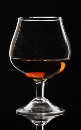 Glass of cognac on black background photo