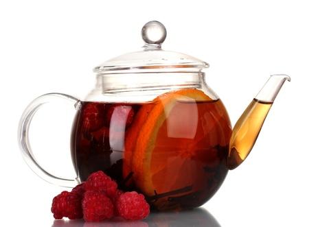 Glass teapot with black tea of raspberries and orange isolated on white photo