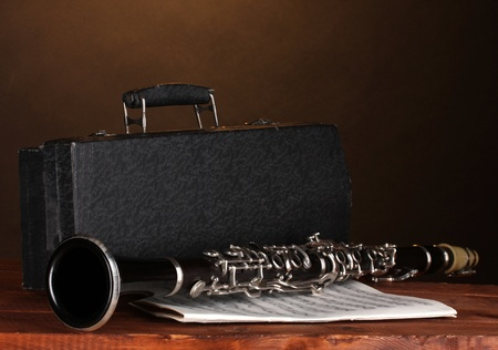 old clarinet, case and notebook with notes on wooden table on brown background photo