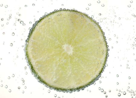 harsh light: slice of lime in the water with bubbles