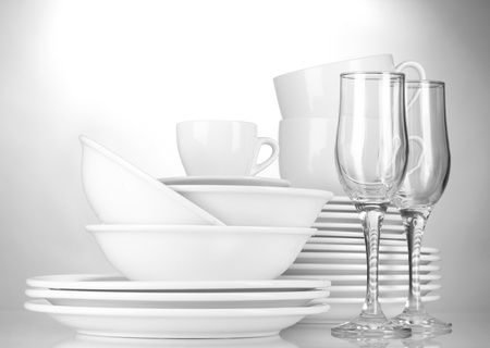 plate setting: empty bowls, plates, cups and glasses on grey background Stock Photo