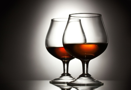 Two glasses of cognac on grey background photo