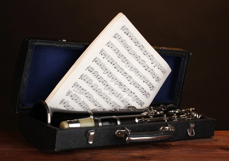 old clarinet and notebook with notes in case on wooden table on brown background photo