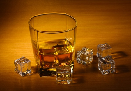 whisky: glass of scotch whiskey and ice on wooden table