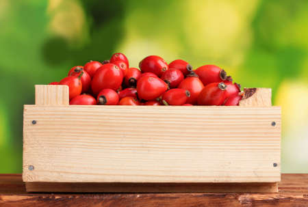briar bush: ripe briar in wooden box on wooden table on green background