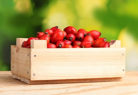 ripe briar in wooden box on wooden table on green background photo