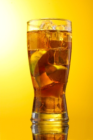 yelow: Iced tea with lemon and lime on yelow background